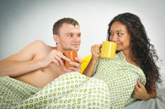 Young couple in bed with coffee Stock Photography