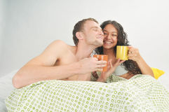 Young couple in bed with coffee Stock Photo
