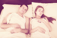 Young couple in bed covered with sheet Royalty Free Stock Photos