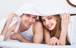 Young couple in bed covered with sheet Royalty Free Stock Images