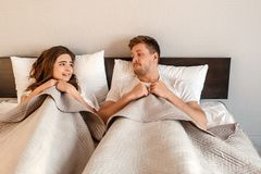 Young couple in the bed. Fear of sex, shy woman and man hidding under blanket before intimacy. Young couple in the bed. Fear of sex, shy women and men hidding royalty free stock photography