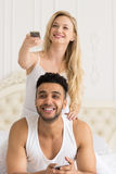 Young Couple In Bed, Happy Smile Hispanic Man And Woman Hold Console Change Channels Stock Image