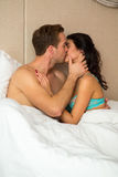 Young couple in bed kissing. Stock Photo