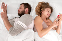 Young couple in bed looking phone and ignoring each other while lying together stock photo