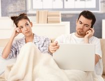 Young couple in bed man working woman bored Stock Photo