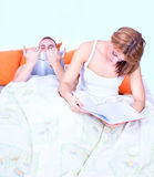 A young couple in bed reading Stock Photos
