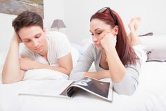 Young couple in bed reading magazine together Stock Photo