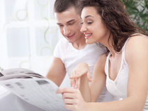 A young couple in bed reading a newspaper Royalty Free Stock Photos