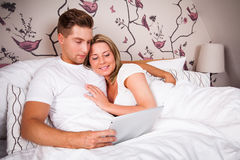 Young couple in bed, reading on tablet computer Royalty Free Stock Images