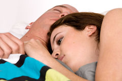 Young couple in bed slowly waking up Royalty Free Stock Photography