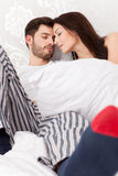 Young couple in bed. Young couple snuggling in bed Royalty Free Stock Photos