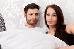 Young couple in bed. Young couple snuggling in bed Royalty Free Stock Photography