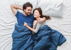 Young couple in bed top view morning concept looking at each other hugging royalty free stock photo