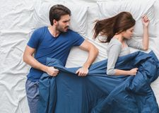 Young couple in bed top view morning concept taking blanket stock photo