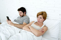 young couple in bed unsatisfied wife bored frustrated and angry while internet addict husband is using mobile phone  social networ Stock Photo
