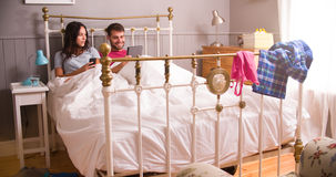 Young Couple In Bed Using Digital Tablet And Mobile Phone Royalty Free Stock Images