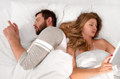 Young couple in bed using phone lying backs to each other. Young couple in bed looking phone and ignoring each other while lying together royalty free stock image