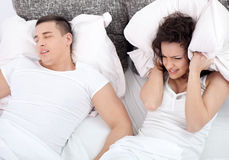 Young couple in bed woman trying to sleep while a man is snoring. Snoring men and young woman. Couple sleeping in bed Stock Image