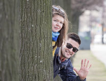 Young couple behind tree Royalty Free Stock Images