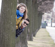 Young couple behind tree Stock Photography