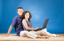 Young couple on beige carpet Stock Image