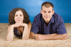 Young couple on beige carpet Royalty Free Stock Images