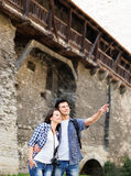 Young couple being tourists exploring the medieval buildings Royalty Free Stock Photo