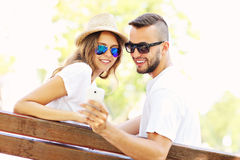 Young couple on a bench with smartphone stock photography