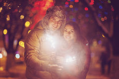 Young couple with Bengal light looking at camera outside Stock Photos