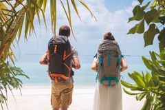Young couple with big backpack walking to the beach in a tropical holiday destination stock photography