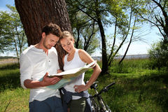 Young couple on a bike ride checking map Stock Photos