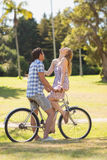 Young couple on a bike ride in the park Stock Images
