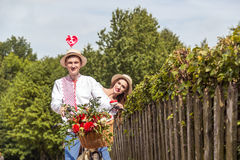 Young couple with bike tandem in park. The girl holds a candy in the form of a heart Royalty Free Stock Photos