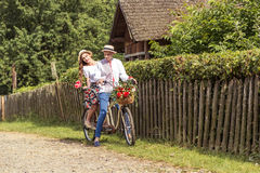 Young couple with bike tandem in park. The girl holds a candy in the form of a heart Stock Photography