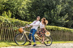 Young couple with bike tandem in park. Young people keep hats in their hands and smile. On the back of the tree fence Royalty Free Stock Image