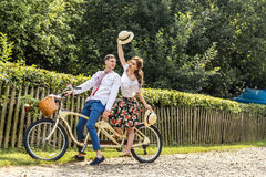 Young couple with bike tandem in park. Young people keep hats in their hands and smile. On the back of the tree fence Royalty Free Stock Images