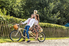 Young couple with bike tandem in park. Young people keep hats in their hands and smile. On the back of the tree fence Stock Photo