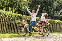 Young couple with bike tandem in park. Young people keep hats in their hands and smile. On the back of the tree fence Stock Image