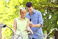 Young couple on bikes checking the cellphone Royalty Free Stock Images