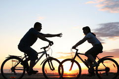 A young couple on bikes riding towards each other. With outstretched arm Stock Image