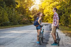 Young couple biking on a forest road in a sammer day royalty free stock photography