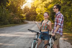 Young couple biking on a forest road in a sammer day royalty free stock image