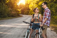 Young couple biking on a forest road in a sammer day stock photo
