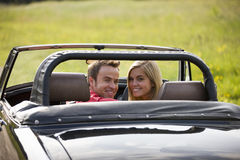 A young couple in a black sports car smiling Stock Photo