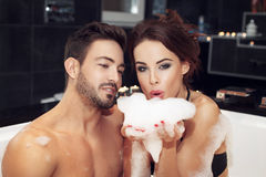 Young couple blow bubble foam in jacuzzi Royalty Free Stock Photos
