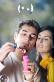 Young couple blowing bubbles. Outdoors Royalty Free Stock Image