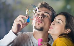 Young couple blowing bubbles. Outdoors Stock Images