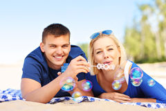Young couple blowing bubbles at the beach Royalty Free Stock Images