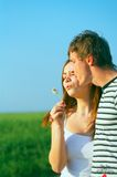 Young couple blowing dandelion Stock Images