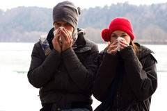 A Young Couple Blowing Their Noses. A Young Couple Next To Each Other Blowing Their Noses And Looking at the camera Royalty Free Stock Photography